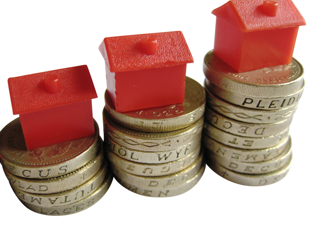 Houses on stacks on coins to represent house prices for September